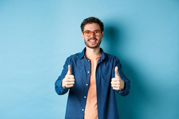 Szczęśliwy młody człowiek w okularach pokazując kciuki do góry, polecając sklep optyka, stojąc na niebieskim tle.
