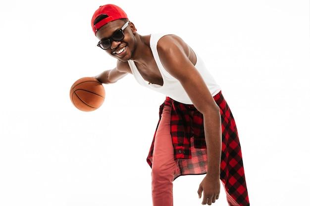 Szczęśliwy młody człowiek w okularach przeciwsłonecznych bawić się z koszykówki piłką