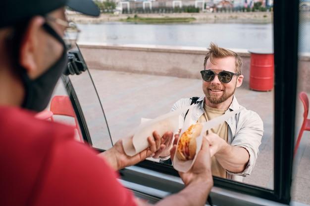 Szczęśliwy młody człowiek w okularach przeciwsłonecznych kupujący fast food