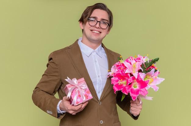 Szczęśliwy młody człowiek w okularach trzymający prezent i bukiet kwiatów uśmiechnięty radośnie, gratulujący z okazji międzynarodowego dnia kobiet stojącego nad zieloną ścianą