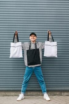Szczęśliwy młody człowiek w stylowe ubranie stoi z torby ekologiczne w dłoniach i pozach
