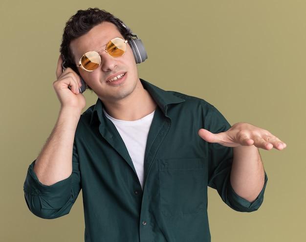 Szczęśliwy młody człowiek w zielonej koszuli w okularach ze słuchawkami, ciesząc się swoją ulubioną muzyką stojąc na zielonej ścianie