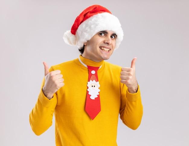 Szczęśliwy młody człowiek w żółtym golfie i czapce mikołaja z zabawnym krawatem patrząc na kamery z uśmiechem na twarzy pokazując kciuki do góry stojąc na białym tle