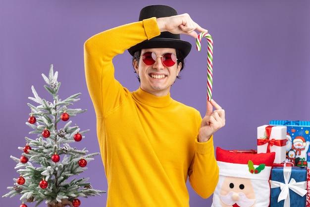 Szczęśliwy młody człowiek w żółtym golfie i okularach w czarnym kapeluszu trzymający cukierkową laskę stojącą obok choinki i prezentów na fioletowej ścianie