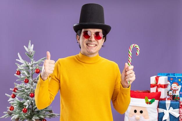 Szczęśliwy młody człowiek w żółtym golfie i okularach w czarnym kapeluszu trzymający laskę cukrową uśmiechnięty, pokazujący kciuki do góry, stojący obok choinki i prezentów na fioletowej ścianie