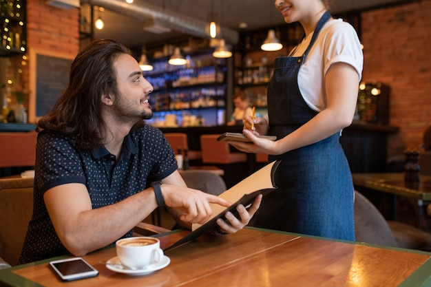 Szczęśliwy młody człowiek, wskazując na menu robiąc zamówienie kelnerka stojąca przed nim i robienia notatek w notatniku