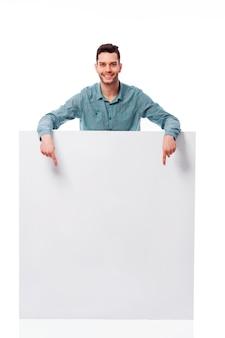Szczęśliwy młody człowiek, wskazując na pustą deskę