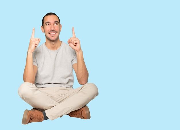 Szczęśliwy młody człowiek wskazuje palcem w górę