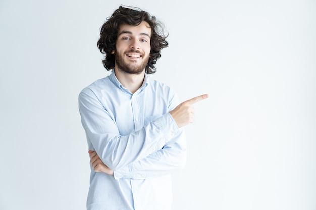 Szczęśliwy młody człowiek wskazuje palec na boku