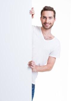 Szczęśliwy młody człowiek wychodzą z pustego transparentu - na białym tle