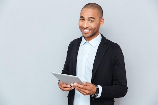 Szczęśliwy młody człowiek z afryki, uśmiechający się i używający tabletu