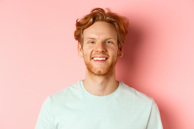 Szczęśliwy młody człowiek z brodą i niechlujną rudą fryzurą, uśmiechnięty z białymi zębami i wesołym wyrazem twarzy, stojący na różowym tle.
