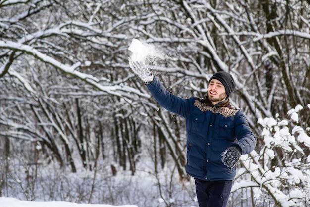 Szczęśliwy młody człowiek z brodą rzuca śnieżki