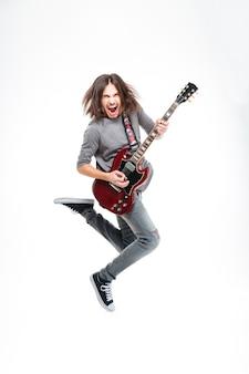 Szczęśliwy młody człowiek z długimi włosami, skaczący i grający na gitarze elektrycznej na białym tle