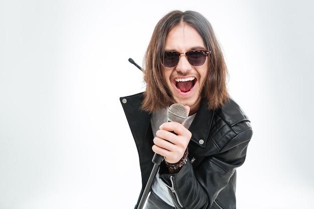 Szczęśliwy młody człowiek z długimi włosami w okularach przeciwsłonecznych za pomocą mikrofonu do śpiewania na białym tle