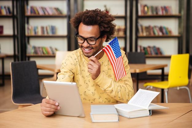 Szczęśliwy młody człowiek z flagą stanów zjednoczonych, uśmiechając się i używając tabletu w bibliotece