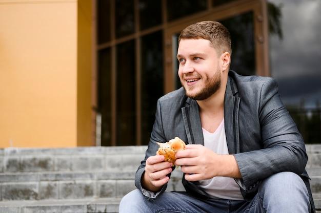 Szczęśliwy młody człowiek z jedzeniem w jego rękach