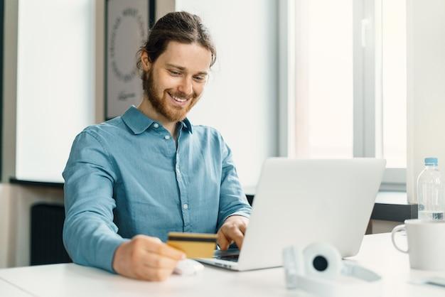 Szczęśliwy młody człowiek z kartą kredytową w ręku robi zakupy online na laptopie