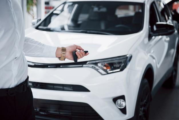 Szczęśliwy młody człowiek z kluczami w rękach, szczęście kupić samochód