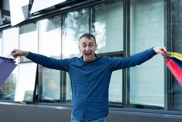 Szczęśliwy młody człowiek z kolorowych toreb na zakupy na ulicy