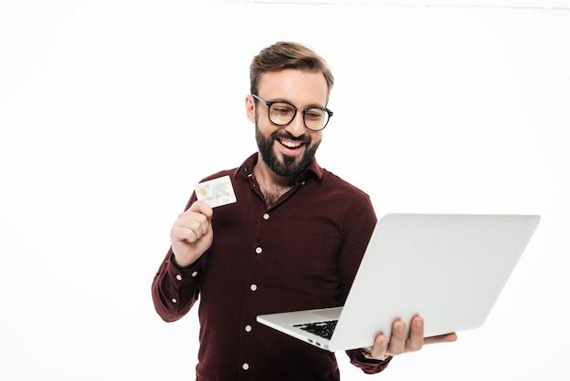 Szczęśliwy młody człowiek z kredytową kartą i laptopem. zakupy internetowe