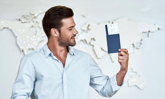 Szczęśliwy młody człowiek z paszportami i biletami w biurze firmy turystycznej