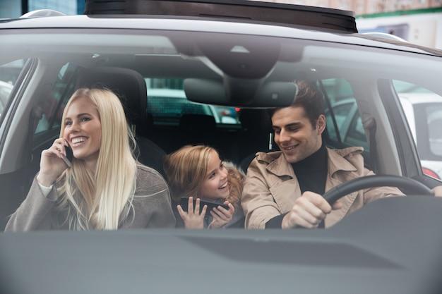 Szczęśliwy młody człowiek z rodziną w samochodzie