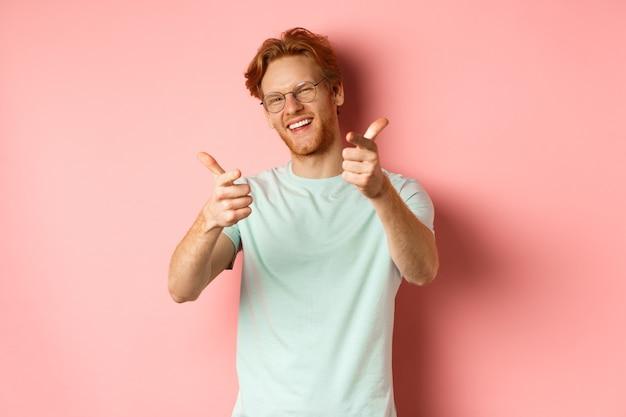 Szczęśliwy młody człowiek z rudymi włosami i brodą, w okularach, mrugający i uśmiechający się, wskazując palcem na...