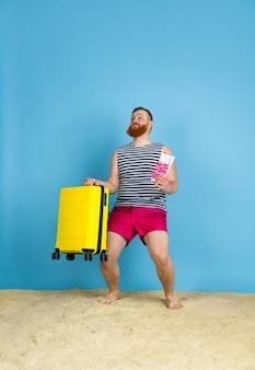 Szczęśliwy młody człowiek z torbą przygotowany do podróży na niebieskiej przestrzeni