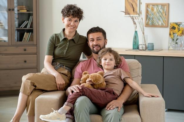 Szczęśliwy młody człowiek z uroczym synkiem i jego śliczną żoną siedzi w dużym miękkim wygodnym fotelu pośrodku salonu w domu