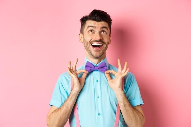 Szczęśliwy młody człowiek z wąsami, dotykając muszki i śmiejąc się, patrząc na logo, stojąc na różowym tle.