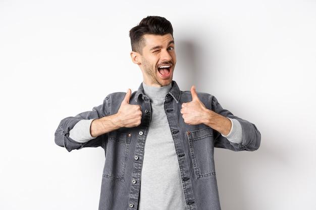 Szczęśliwy młody człowiek z wąsem mrugający i pokazujący kciuki do góry, polecający coś, chwalący dobrą rzecz, robiąc komplement, stojąc na białym tle.