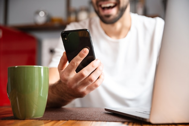Szczęśliwy młody człowiek za pomocą komputera przenośnego siedząc przy kuchennym stole, trzymając telefon komórkowy