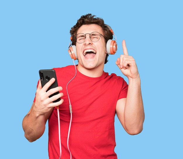 Szczęśliwy młody człowiek za pomocą słuchawek i smartfona