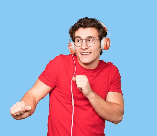 Szczęśliwy młody człowiek za pomocą słuchawek