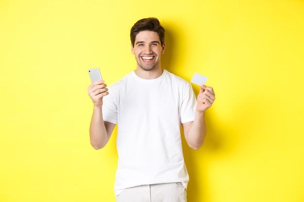 Szczęśliwy młody człowiek zakupy online w smartfonie, trzymając kartę kredytową i uśmiechnięty, stojąc na żółtym tle.
