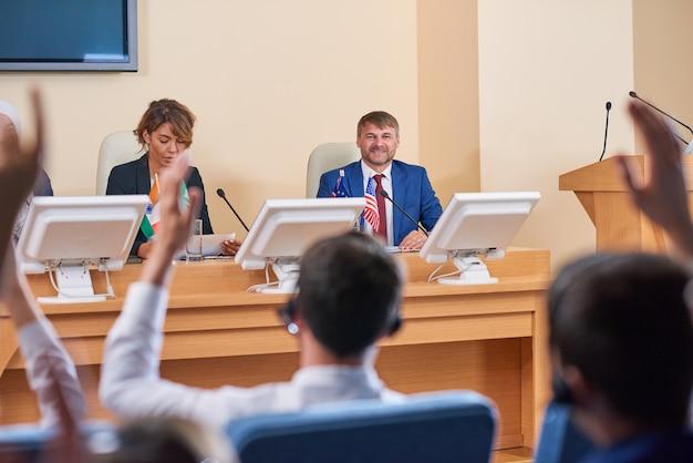 Szczęśliwy młody delegat w wizytowym stroju, patrząc z uśmiechem na publiczność, siedząc przed nimi i słuchając ich pytań