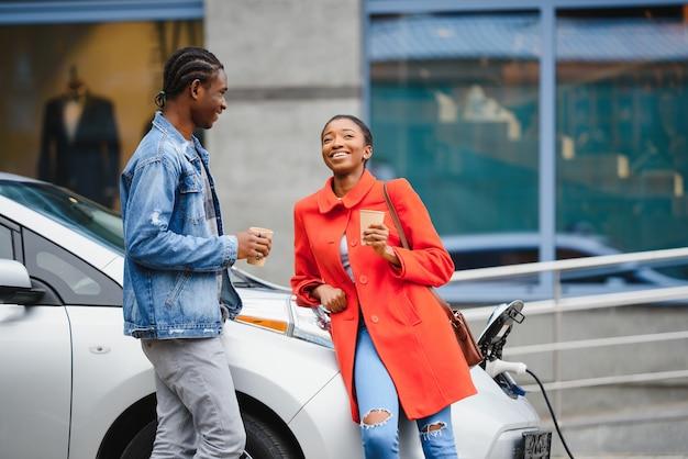 Szczęśliwy młody dorosły człowiek afroamerykanin i uśmiechnięta kobieta ładowania samochodu elektrycznego.