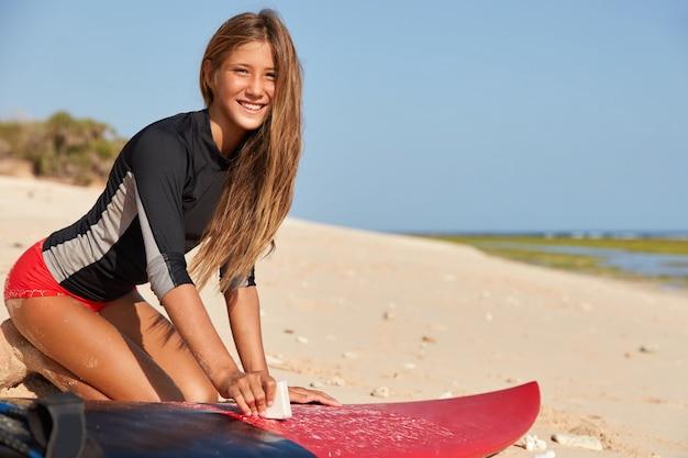Szczęśliwy młody doświadczony surfingowiec nosi czerwone bikini, ma opaloną skórę, zdrowe ciało, woskuje deskę surfingową