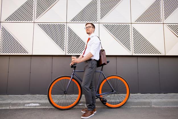 Szczęśliwy młody elegancki człowiek z rowerem stojący w środowisku miejskim na zewnątrz współczesnej architektury, idąc do domu