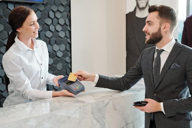 Szczęśliwy młody elegancki mężczyzna trzyma kartę kredytową nad maszyną płatniczą przed sprzedawcą przy zakupie nowych ubrań w butiku