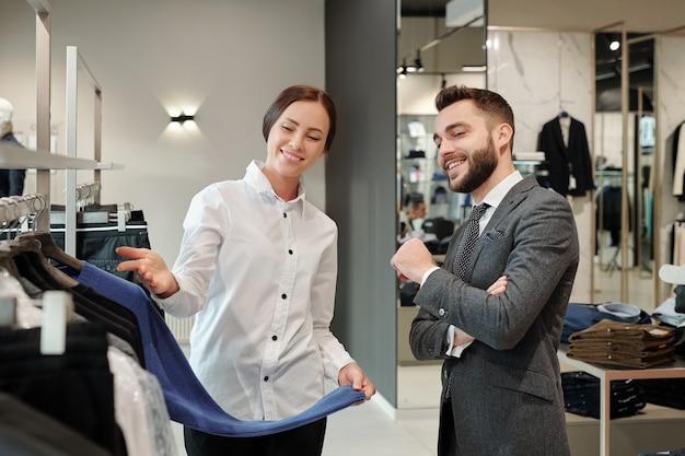 Szczęśliwy młody elegancki mężczyzna w szarym garniturze konsultuje się ze sprzedawcą, szukając nowego swetra w butiku