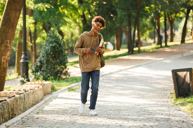 Szczęśliwy młody facet z plecakiem spacerujący po parku