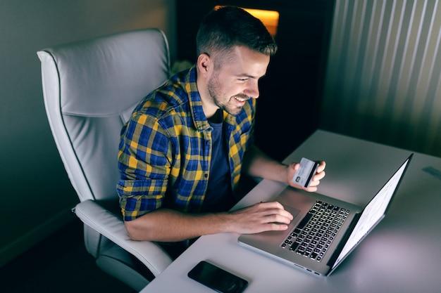 Szczęśliwy młody freelancer za pomocą karty kredytowej do płacenia rachunków online. w jednej ręce karta kredytowa, a druga w laptopie