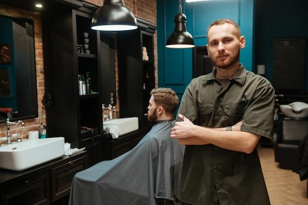 Szczęśliwy młody fryzjer stojący w pobliżu swojego klienta.