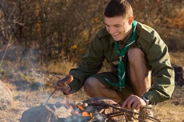 Szczęśliwy młody harcerz grillowania kiełbasek do jedzenia na ziemi na terenie obozu.