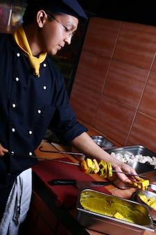Szczęśliwy młody i atrakcyjny szef kuchni