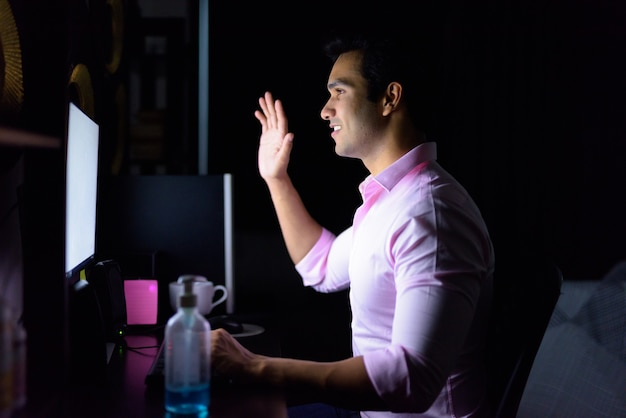 Szczęśliwy młody indyjski biznesmen rozmowy wideo podczas pracy w godzinach nadliczbowych w domu podczas kwarantanny w ciemności
