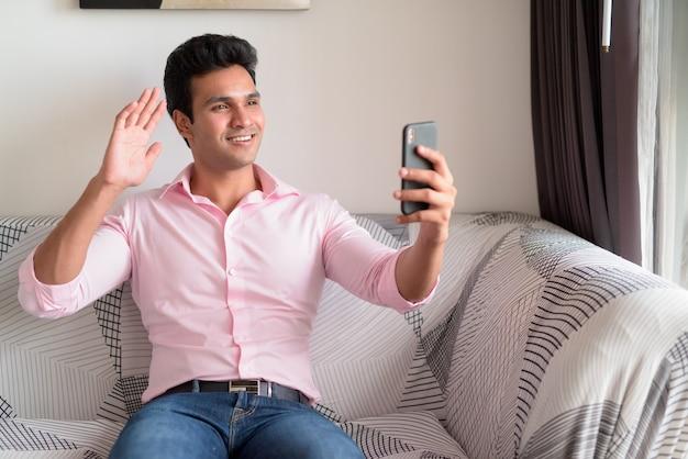 Szczęśliwy młody indyjski biznesmen rozmowy wideo z telefonu w domu