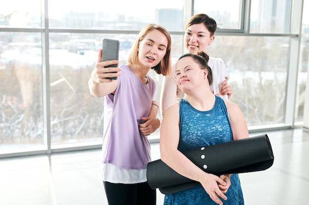 Szczęśliwy młody instruktor fitness i dwie aktywne kobiety patrząc na smartfona podczas robienia selfie po treningu